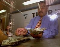 Un empleado cuenta dólares en una casa de cambios en Ciudad de México. Las remesas a México crecieron un 5.5 por ciento en diciembre a tasa interanual, anotando su mayor alza desde septiembre, pero la cifra acumulada del año mostró una caída frente al 2012, según datos divulgados el martes por Banco de México (central). Reuters/Archive