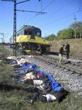 Тела жертв столкновения микроавтобуса с поездом в Днепропетровской области на Украине 12 октября 2010 года. Как минимум 12 человек погибли во вторник при столкновении маршрутки с поездом на железнодорожном переезде в Сумской области на северо-востоке Украины, где подобные ДТП уже приводили к гибели множества людей. REUTERS/Pool