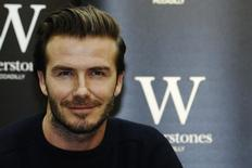 "Retired soccer player David Beckham poses with his book ""David Beckham"" at a bookshop in London December 19, 2013. REUTERS/Luke MacGregor"