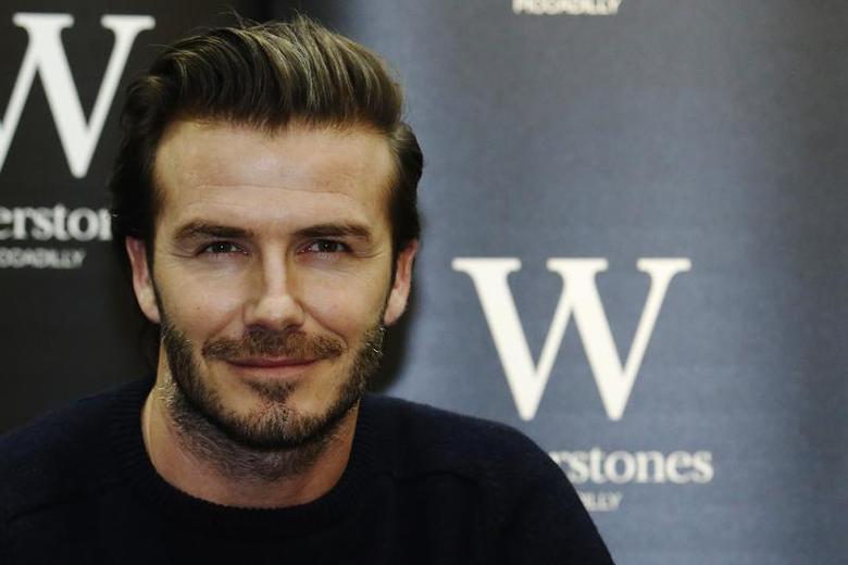 Retired soccer player David Beckham poses with his book ''David Beckham'' at a bookshop in London December 19, 2013. REUTERS/Luke MacGregor