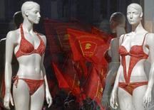 Коммунистические флаги участников митинга отражаются в витрине магазина в Санкт-Петербурге 1 мая 2013 года. Юлмарт, первый онлайн-ритейлер в РФ, получивший свыше $1 миллиарда выручки в прошлом году, планирует в 2014-м приблизиться к отметке в $2 миллиарда, а в следующем выйти на самоокупаемость и начать интеграцию с другими игроками рынка, чтобы получить крупнейшую в стране платформу для интернет-продаж товаров со своей логистикой и сервисом. REUTERS/Alexander Demianchuk