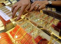 Продавец ювелирного магазина в Ханое пересчитывает золотые слитки 23 августа 2011 года. Цены на золото закрепились выше $1.250 за тройскую унцию на фоне незначительного роста на фондовых рынках Азии из-за опасений за рост мировой экономики. REUTERS/Kham
