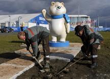 Рабочие копают в Олимпийском парке в Адлере рядом с Сочи 4 февраля 2014 года. Дорогостоящая Олимпиада в Сочи вряд ли даст ощутимый толчок российской экономике, заявило в среду агентство Moody's, развенчав одну из основных целей президента Владимира Путина на этих Играх. REUTERS/Alexander Demianchuk