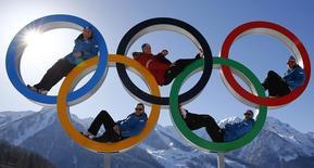 Esquiadores austríacos posam para foto dentro dos anéis olímpicos, em Sochi, na Rússia. O Comitê Olímpico Internacional (COI) começou a receber na quarta-feira sugestões destinadas a manter a popularidade e lucratividade dos Jogos Olímpicos nos próximos anos, o que inclui medidas para baratear as candidaturas das cidades anfitriãs e até a possibilidade de realizar os eventos em mais de uma sede. 4/02/2014. REUTERS/Kai Pfaffenbach