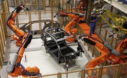 Un trabajador ajusta unos robots en la planta de producción del vehículo eléctrico i3 de BMW en la planta de la firma en Leipzig, Alemania, sep 18 2013. El crecimiento global permaneció sólido a comienzos del 2014 y apuntó a una expansión trimestral del producto interno bruto (PIB) de un 3 por ciento, según un informe publicado el miércoles que mostró que los manufactureros volvieron a liderar el alza. REUTERS/Fabrizio Bensch