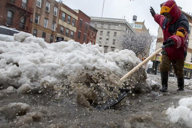A worker clears snow and ice from a sewer drain in the Park Slope section of Brooklyn New York following an overnight snow storm February 5, 2014. REUTERS/Brendan McDermid