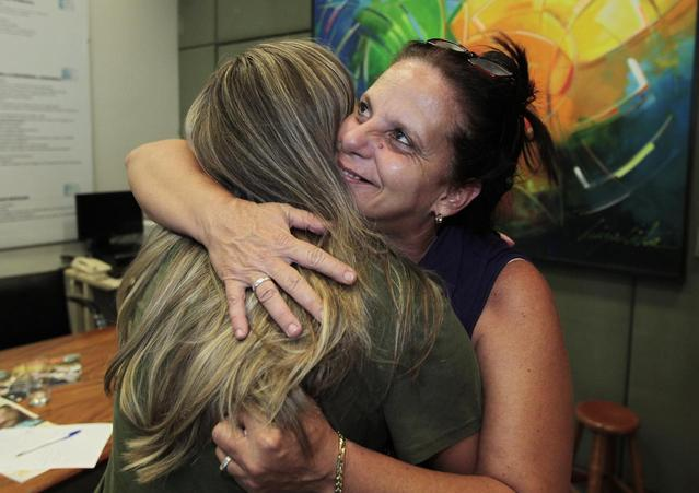 Cuban doctor, Ramona Rodriguez (R), 51, embraces an unidentified person in the office of the center-right Democratas Party where she presented her request for political asylum in Brasilia, February 5, 2014. REUTERS/Joedson Alves