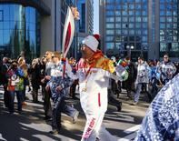 United Nations Secretary-General Ban Ki-moon runs with the 2014 Sochi Olympics torch as the torch relay arrives in Sochi February 6, 2014. REUTERS/Shamil Zhumatov