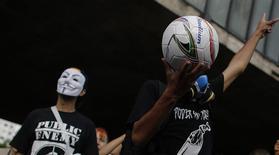 Um homem segura uma bola de futebol durante um protesto contra a Copa do Mundo de 2014, em São Paulo. As forças de segurança brasileiras estão usando agentes à paisana, interceptando e-mails e monitorando rigorosamente a mídia social para tentar garantir que protestos violentos contra o governo não arruínem a Copa do Mundo, disseram autoridades à Reuters. 25/01/2014 REUTERS/Nacho Doce