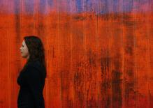 "An employee poses with a detail of artist Gerhard Richter's artwork ""Wand (Wall)"" at Sotheby's auction house in London January 29, 2014. REUTERS/Luke MacGregor"