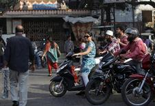 A woman riding a scooter waits for a traffic signal along a street in Mumbai February 5, 2014. REUTERS/Mansi Thapliyal