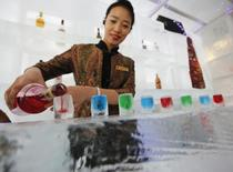 Официантка разливает алкоголь в рюмки изо льда в отеле Shangri-La в Харбине 6 января 2014 года. Активность в секторе услуг Китая выросла с минимальной почти за 2,5 года скоростью в январе 2014 года, в очередной раз подтвердив замедление второй по величине экономики мира. REUTERS/Kim Kyung-Hoon