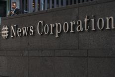 Мужчина стоит у офиса News Corporation в Нью-Йорке 28 июня 2012 года. Медиахолдинг Руперта Мердока News Corp уменьшил выручку в четвертом квартале 2013 года на 4 процента из-за снижения доходов от рекламы в принадлежащих ему газетах, но сокращение расходов помогло компании превзойти ожидания аналитиков в части прибыли. REUTERS/Keith Bedford
