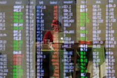 Котировки филиппинских акций отражаются в стеклянной панели в Маниле 6 февраля 2014 года. Отток средств из глобальных фондов, инвестирующих в развивающиеся рынки, достиг исторического рекорда, а для ориентированных на РФ фондов последняя неделя стала восьмой в цикле бегства капитала. REUTERS/Romeo Ranoco