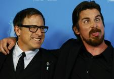 Actor Christian Bale (R) and director David O. Russell pose to promote the movie American Hustle at the 64th Berlinale International Film Festival in Berlin February 7, 2014. The festival runs from February 6 until 16 in the German capital. REUTERS/Tobias Schwarz