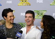 """Alex Kinsey (L) and Sierra Deaton (R) look at their mentor and judge Simon Cowell (C) as he speaks during an interview backstage after the folk duo won """"The X Factor """" in Los Angeles, California, December 19, 2013. REUTERS/Kevork Djansezian"""