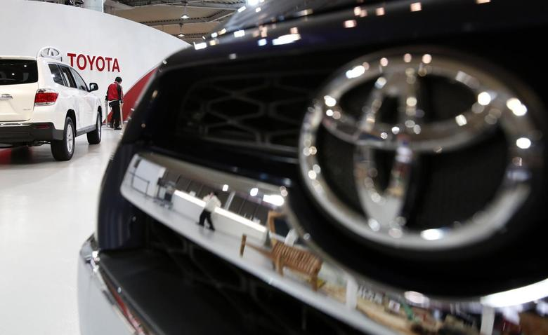 A showroom staff member works under the logo of Toyota Motor Corp, between cars displayed at its showroom in Tokyo February 4, 2014. REUTERS/Yuya Shino