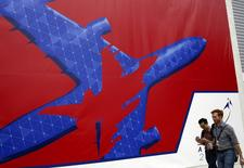 People walk past a Singapore Airshow poster at the exhibition venue in Singapore February 7, 2014. REUTERS/Edgar Su