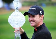Feb 9, 2014; Pebble Beach, CA, USA; Jimmy Walker celebrates with the championship trophy after his victory during the final round of the AT&T Pebble Beach Pro-Am at Pebble Beach Golf Links. Mandatory Credit: Allan Henry-USA TODAY Sports