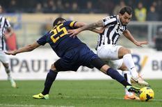 Carlos Tevez, do Juventus, disputa a bola com Rafael Marques, do Hellas Verona, durante partida no Estádio Bentegodi em Verona, Itália. 9/2/2014 REUTERS/Giorgio Perottino