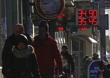 Люди проходят мимо вывески пункта обмена валюты в Москве 30 января 2014 года. Рубль торговался с незначительными изменениями в течение спокойной сессии понедельника перед важными событиями и публикациями в США, Китае и еврозоне, а днем протестировал возможную новую границу повышенных валютных интервенций ЦБ. REUTERS/Maxim Shemetov