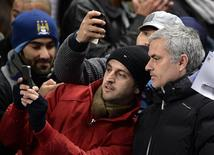 Chelsea manager Jose Mourinho (R) has his photograph taken with fans before their English Premier League soccer match against Manchester City at the Etihad Stadium in Manchester, northern England, February 3, 2014. REUTERS/Nigel Roddis