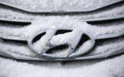 The logo of Hyundai Motor on a sedan is covered with snow at a shipping yard of South Korea's biggest automakers Hyundai Motor Co and affiliate Kia Motors Corp at a port in Pyeongtaek, about 70 km (43 miles) south of Seoul January 20, 2014. REUTERS/Kim Hong-Ji