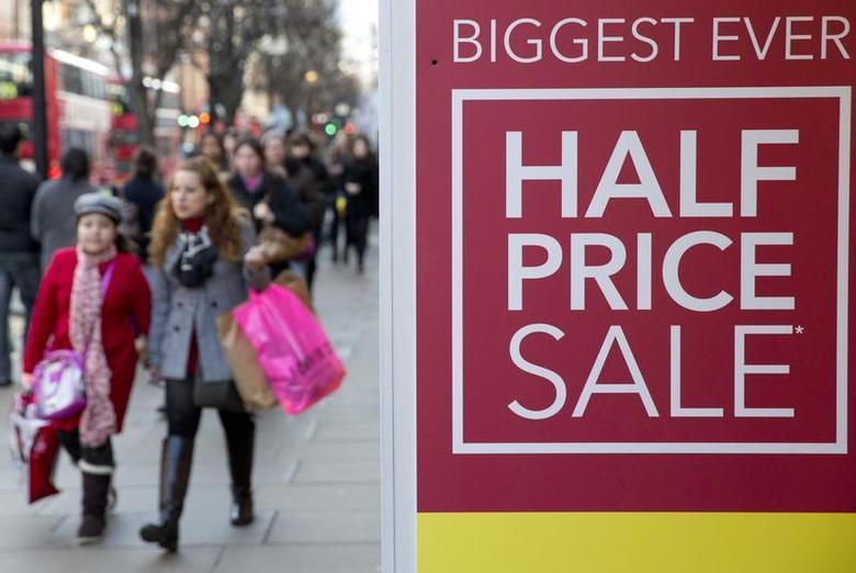 Shoppers walk past a sale sign on Oxford Street in central London December 29, 2013. REUTERS/Neil Hall