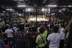 "Spectators follow a fight during the closing Thai boxing, or ""Muay Thai"", fight night of the legendary Lumpinee stadium, one of Bangkok's oldest boxing venues which is being demolished after 57 years, February 7, 2014. REUTERS/Damir Sagolj"