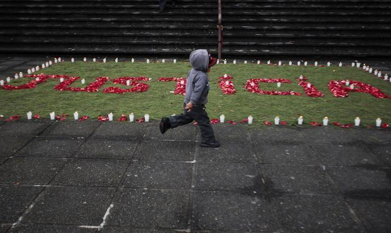 A child runs past an arrangement of flowers and candles that reads: ''Justicia'' (or Justice) in front of the Supreme Court at Guatemala City August 2, 2011. Guatemala on Tuesday sentenced four soldiers belonging to an elite unit known as the Kaibiles, to 6,060 years of prison each, in the first conviction for a massacre during the country's brutal 36-year civil war. More than 200 people were killed when Guatemalan soldiers attacked the northern village of Las Dos Erres in 1982 at the height of Guatemala's civil war. REUTERS/Jorge Dan Lopez