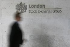 Человек проходит мимо вывески Лондонской фондовой биржи 11 октября 2013 года. Европейские фондовые рынки поднялись до двухнедельного максимума благодаря высоким квартальным показателям ряда компаний и надежде на сохранение мягкой политики ФРС при новом руководстве. REUTERS/Stefan Wermuth