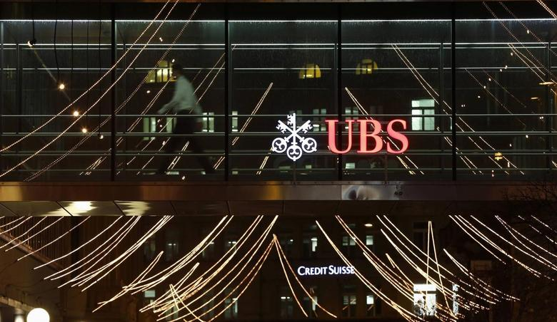 A man walks past the logo of Swiss Bank UBS on a footbridge connecting two office buildings in Zurich December 19, 2013. REUTERS/Arnd Wiegmann