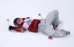 Юки Цубота из Канады после падения во ходе соревнований горных лыжниц в Роза Хутор на Олимпиаде в Сочи 10 февраля 2014 года. Потепление в олимпийском Сочи мешает запланированным на вторник соревнованиямм, а организаторы готовятся к ухудшению ситуации: согласно прогнозу, в течение недели температуры могут еще подрасти. REUTERS/Mike Blake