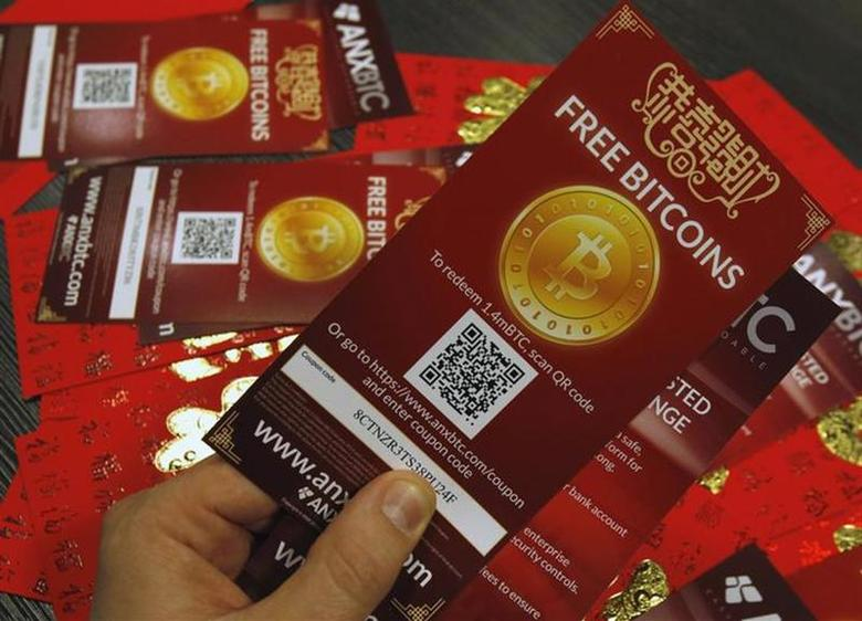 An employee of a bitcoin exchange company displays bitcoin vouchers, which are worth around HK$9 (US$1.15), in Hong Kong February 11, 2014. REUTERS/Bobby Yip
