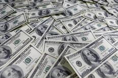 """Долларовые купюры в банке в Сеуле 9 февраля 2013 года. Палата представителей США во вторник одобрила годовое продление полномочий правительства на проведение заимствований после того, как республиканцы уступили требованиям президента Барака Обамы разрешить повышение долгового """"потолка"""" без каких-либо условий. REUTERS/Lee Jae-Won"""