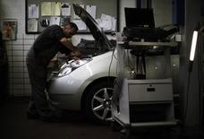 Механик осматривает Toyota Prius II в автосервисе в Цюрихе 14 ноября 2012 года. Toyota Motor Corp объявила в среду об отзыве всех 1,9 миллиона автомобилей Prius третьего поколения, проданных по всему миру, из-за дефекта в программном обеспечении гибридной системы. REUTERS/Michael Buholzer