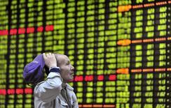 Мужчина изучает электронное табло с котировками на бирже в Цзюцзяне 23 апреля 2013 года. Азиатские фондовые рынки выросли в среду за счет высоких внешнеторговых показателей Китая и приверженности ФРС сворачиванию стимулов. REUTERS/Stringer