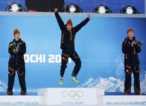 Gold medalist Sven Kramer (C) of the Netherlands jumps on the podium next to his compatriots silver medalist Jan Blokhuijsen (L) and bronze medalist Jorrit Bergsma during the medal ceremony for the men's 5,000 metres speed skating race in the Olympic Plaza at the 2014 Sochi Winter Olympics February 9, 2014. REUTERS/Marko Djurica