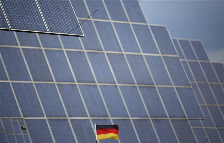 A German national flag is pictured in front of solar panels in Bad Hersfeld May 14, 2013. REUTERS/Lisi Niesner