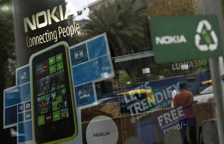 A man is reflected on the glass door of a Nokia showroom in New Delhi March 28, 2013. REUTERS/Mansi Thapliyal/Files