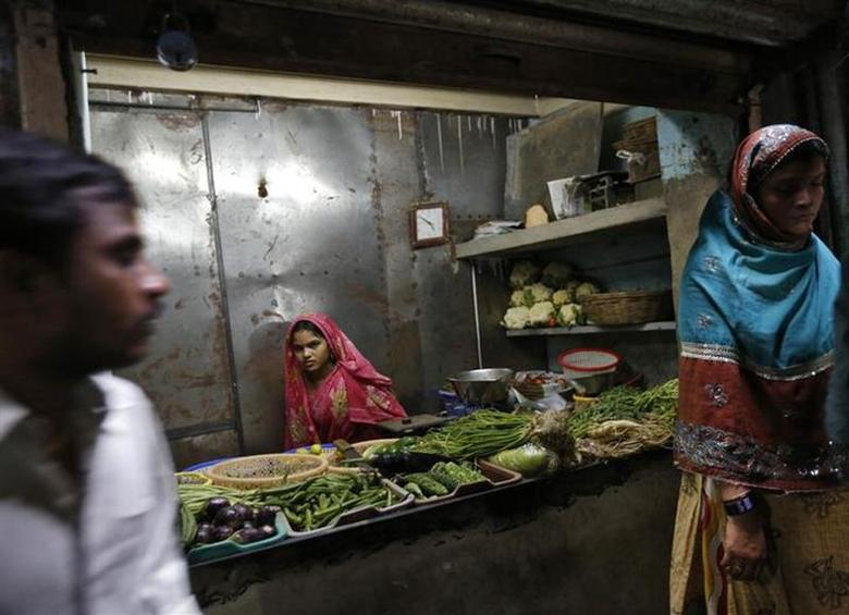A vendor waits for customers at her shop selling vegetables in Dharavi in Mumbai January 24, 2014. REUTERS/Mansi Thapliyal