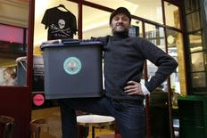 Stephan Martinez, owner of Le Petit Choiseuil bistrot, poses with a garbage container to collect food waste in Paris February 12, 2014. REUTERS/Charles Platiau