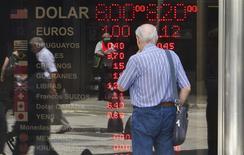 Un hombre observa un panel en una casa de cambio en Buenos Aires, ene 31 2014. Los precios minoristas en Argentina se habrían disparado en promedio un 5,5 por ciento en enero tras una devaluación del peso de un 17 por ciento a mediados de ese mes, en el que sería el mayor aumento de la tasa de inflación desde inicios del 2002, mostró el miércoles un sondeo de Reuters. REUTERS/Stringer