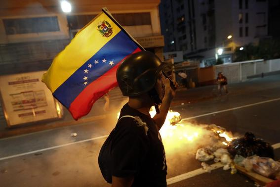 An opposition demonstrator carries a Venezuelan flag as he walks past a burning barricade during a protest in Caracas February 12, 2014. REUTERS-Jorge Silva