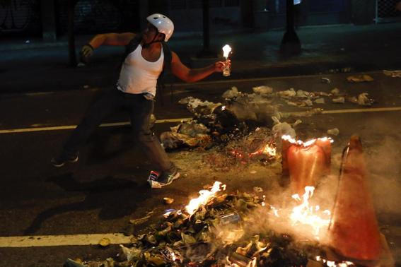 A demonstrator throws a molotov cocktail during a protest against Venezuela's President Nicolas Maduro's government in Caracas February 12, 2014. REUTERS-Carlos Garcia Rawlins