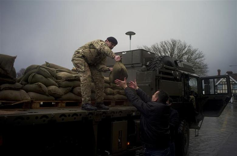 Army sandbags are unloaded to a local shopkeeper in the flooded central square in the village of Datchet in Berkshire, southern England February 12, 2014. REUTERS/Kieran Doherty
