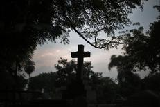 A grave with a cross is seen during sunset at Nicholson Christian Cemetery in old quarters of Delhi February 13, 2014. REUTERS/Adnan Abidi