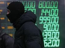 Антиправительственный демонстрант проходит мимо обменного пункта в Киеве 7 февраля 2014 года. Правительство Украины пообещало влить в задолжавшую за российский газ госкомпанию Нафтогаз эквивалент $1,3 миллиарда, источником которых - после сложной схемы с выпуском облигаций - могут стать валютные резервы центробанка, истощившиеся в борьбе с ослаблением гривны на фоне политического кризиса. REUTERS/Gleb Garanich