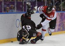 Canada's Rick Nash is flipped in the air by Austria's Florian Iberer during the third period of their men's preliminary round hockey game at the 2014 Sochi Winter Olympic Games, February 14, 2014. REUTERS/Phil Noble