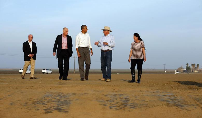 U.S. President Barack Obama walks with farmers Joe Del Bosque and Maria Del Bosque as he tours a drought affected farm field in Los Banos, California February 14, 2014. REUTERS/Kevin Lamarque